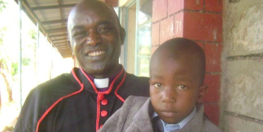 Father John Karimi who quit the Catholic Church in protest against celibacy holding his biological son at Good Samaritan Secondary School in Kirinyaga County after his consecration as a Bishop in the Ecumenical Catholic Church of Christ. He quit Catholic Church and married protesting that celibacy was not practical and should be scrapped.